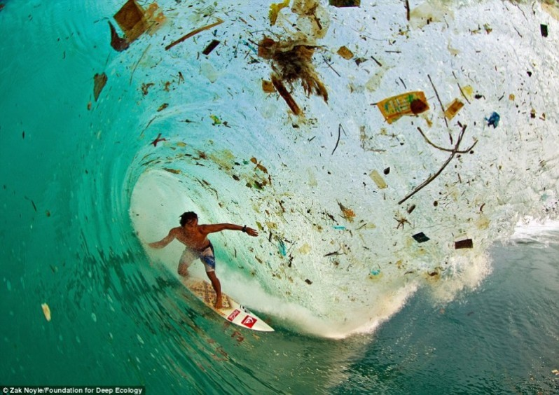 The Indonesian surfer Dede Surinaya rides a wave of filth and trash (Java, Indonesia).